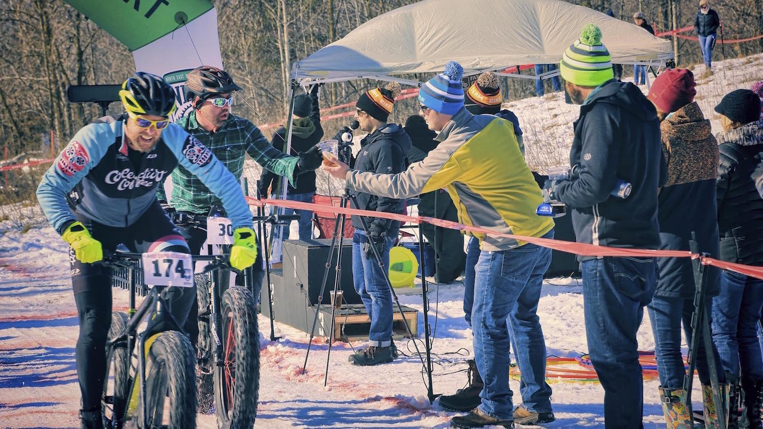Matt Fisher from Recyclist Bicycle Company hands a beer to a  fat bike racer during the Fat Cupid Classic.
